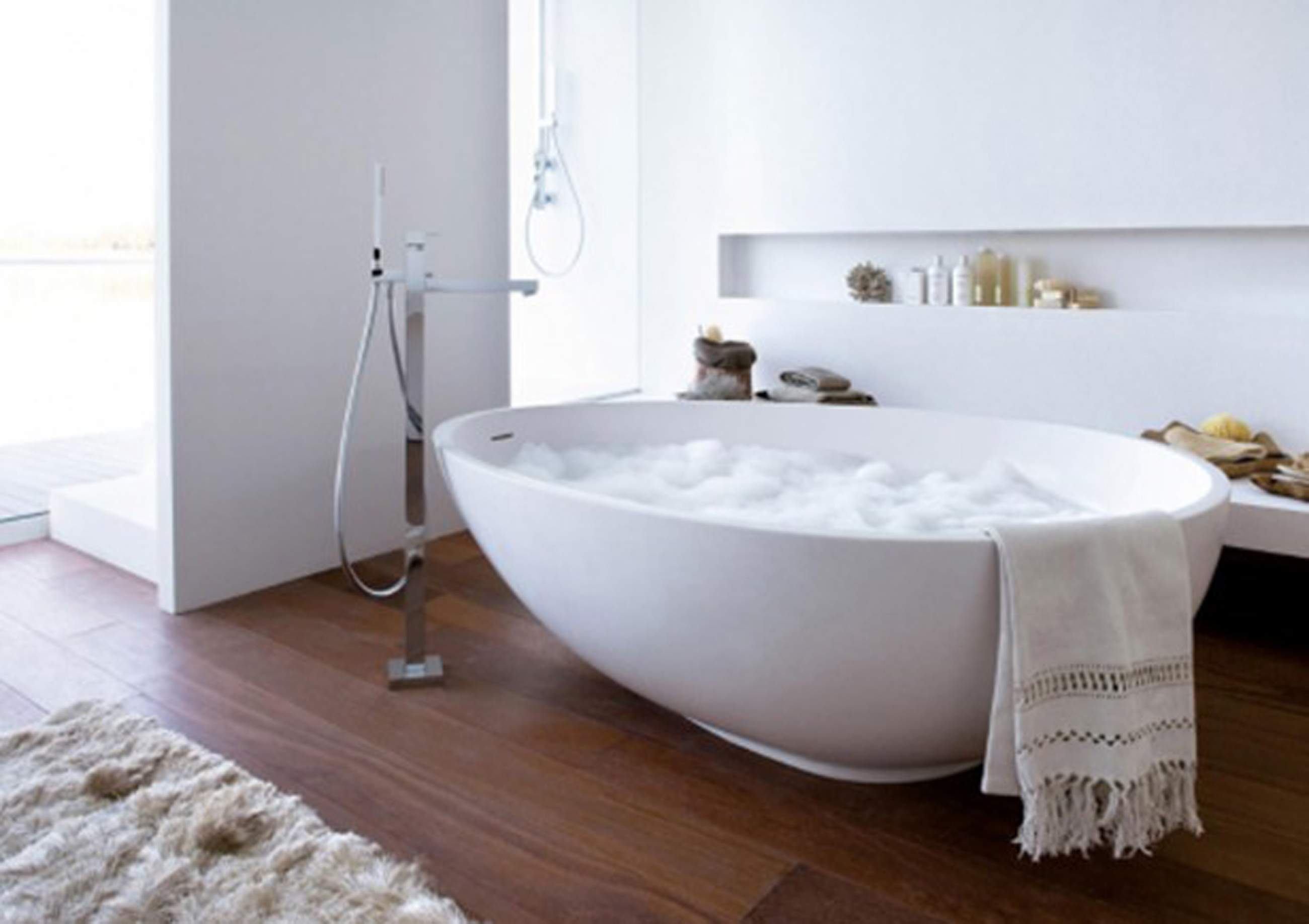 Simple Bathroom Fascinating White Bathtub Design Idea With White Wall With Open Shelf Plus Bottles And Brownhardwood Floor Tile Fascinating Bathtub Design Ideas (View 2 of 23)