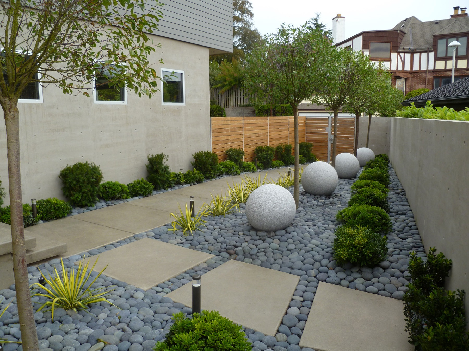 Contemporary Garden Landscape Boasts River Rock And Granite Orbs (Image 9 of 35)