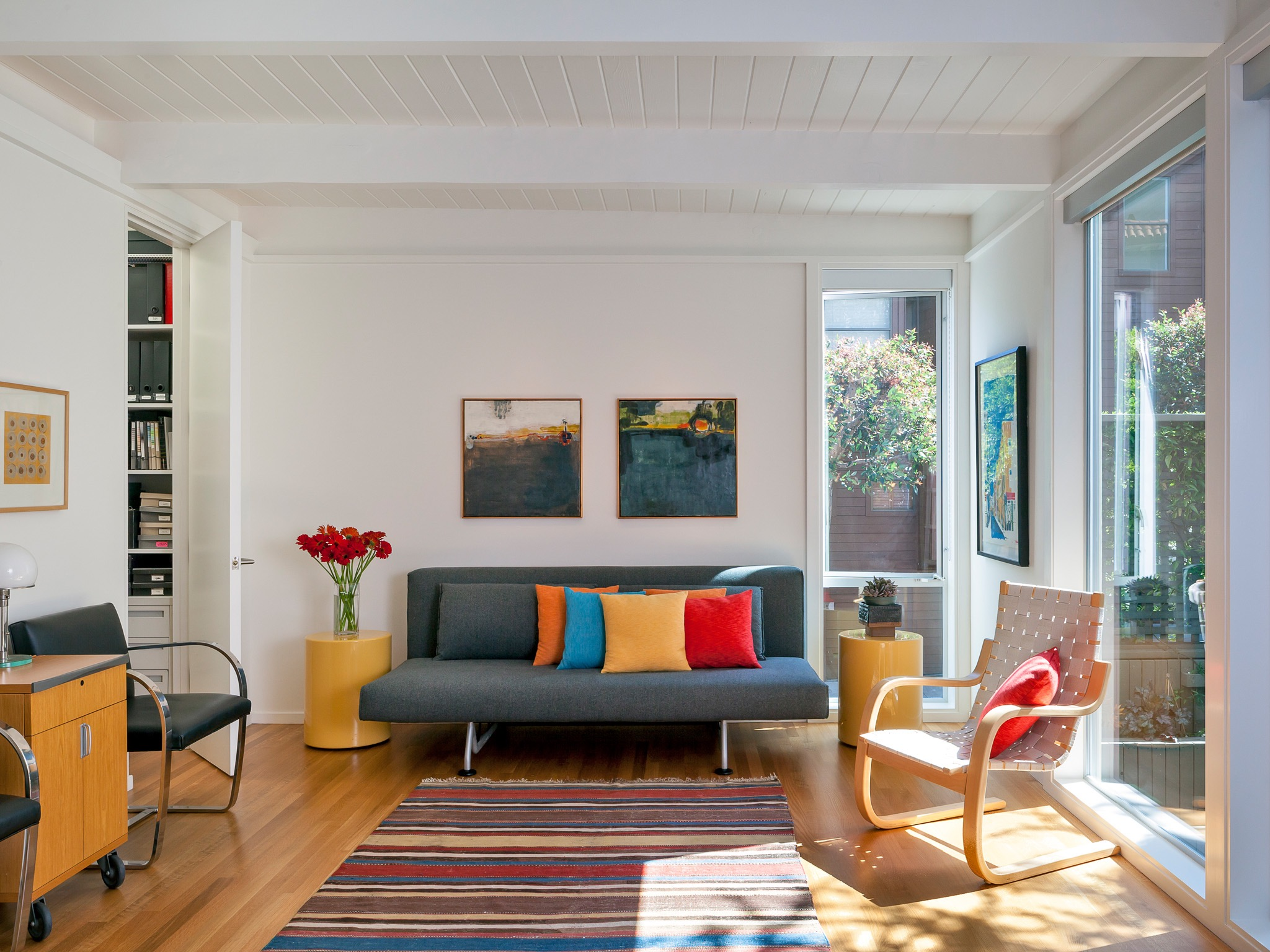 Narrow Living Room With Large Glass Windows And Colorful Throw Pillows (Image 12 of 22)