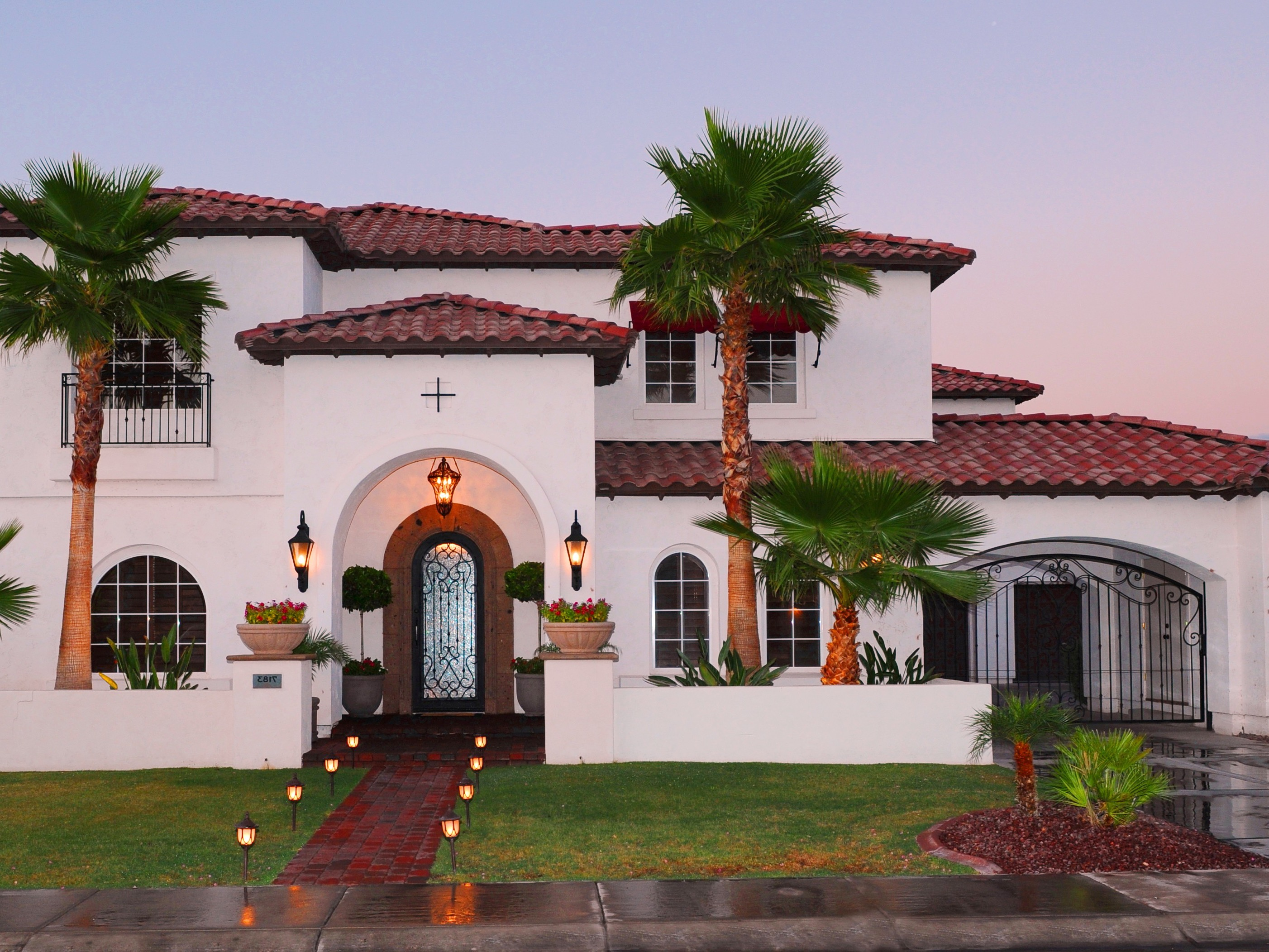 Mediterranean Exterior Of Traditional Spanish Style Home With Brick Walkway, Arched Entryway, Red Tile Roof And Landscape Lighting (Image 17 of 30)