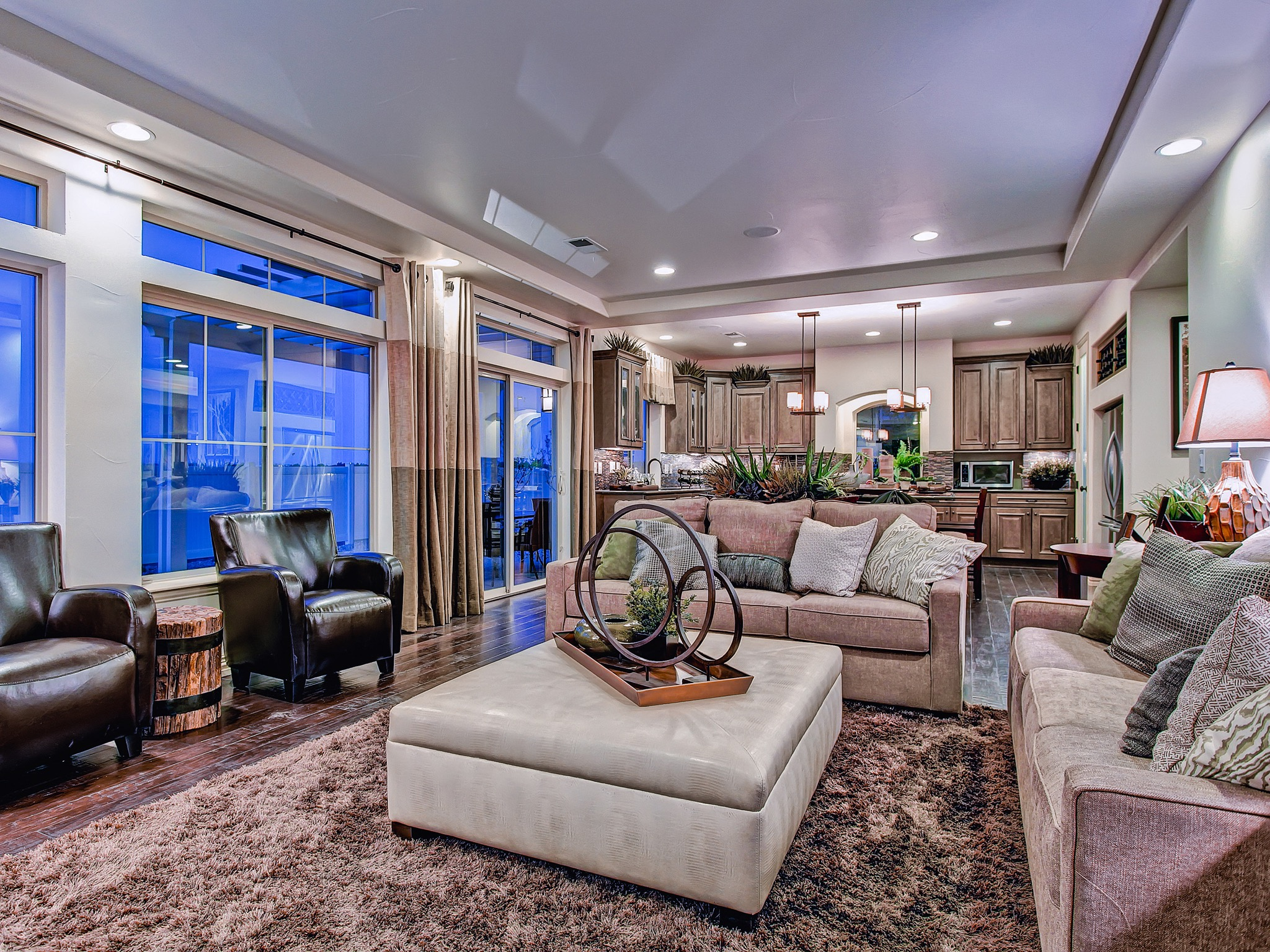 Classic Luxury Living Room With Neutral Ottoman, Large Windows And Tan Sofa (Image 1 of 32)