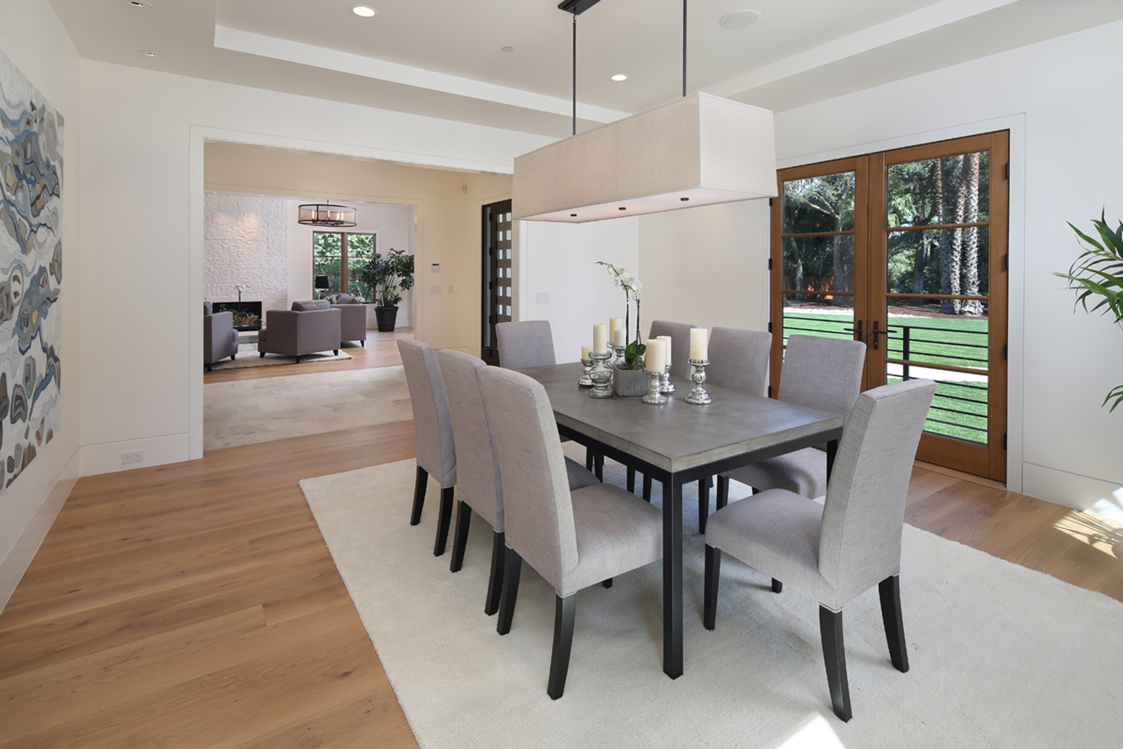 Modern Minimalistic Dining Room With Soft Gray Chairs, Black Dining Table, And Rectangular Chandelier Hangs Above (Image 22 of 30)