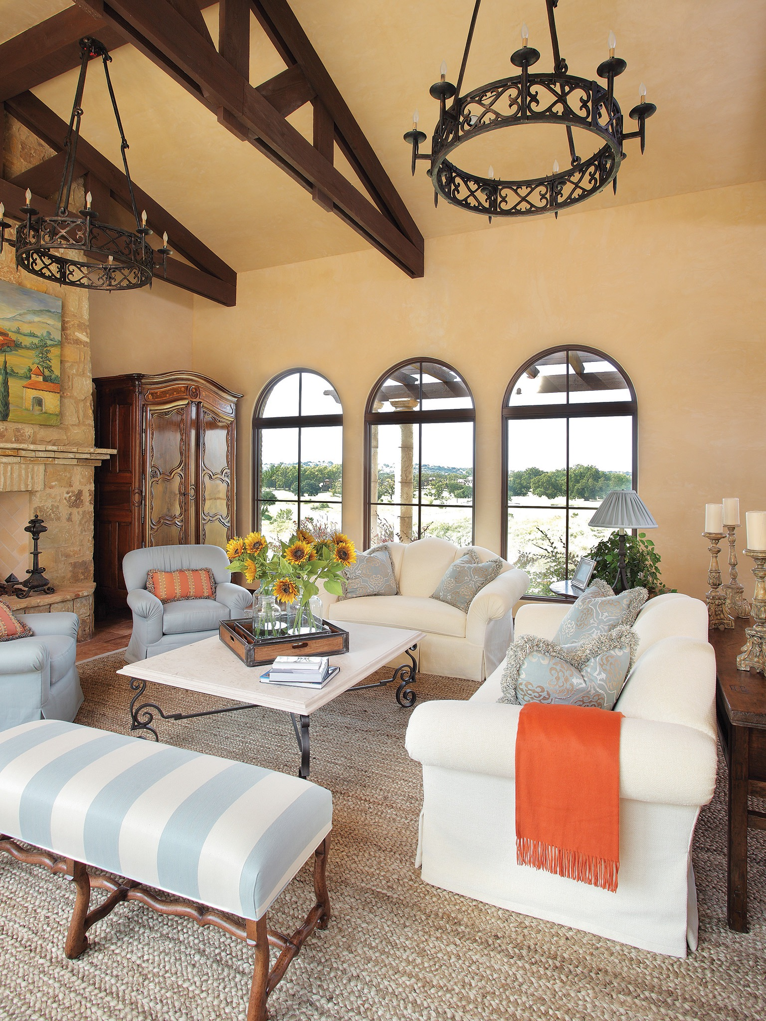 Traditional Italian Living Room With Iron Chandeliers, Arched Windows And A Stone Fireplace (Image 19 of 20)