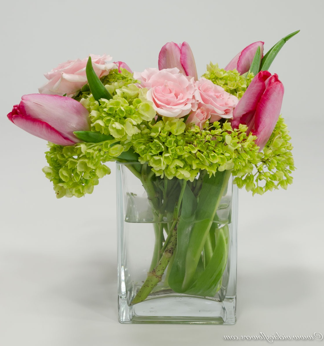 Fresh And Green Wedding Centerpiece With Pink Tulips And Pink Roses Accented With Green Hydrange In Glass Vase (Image 5 of 15)