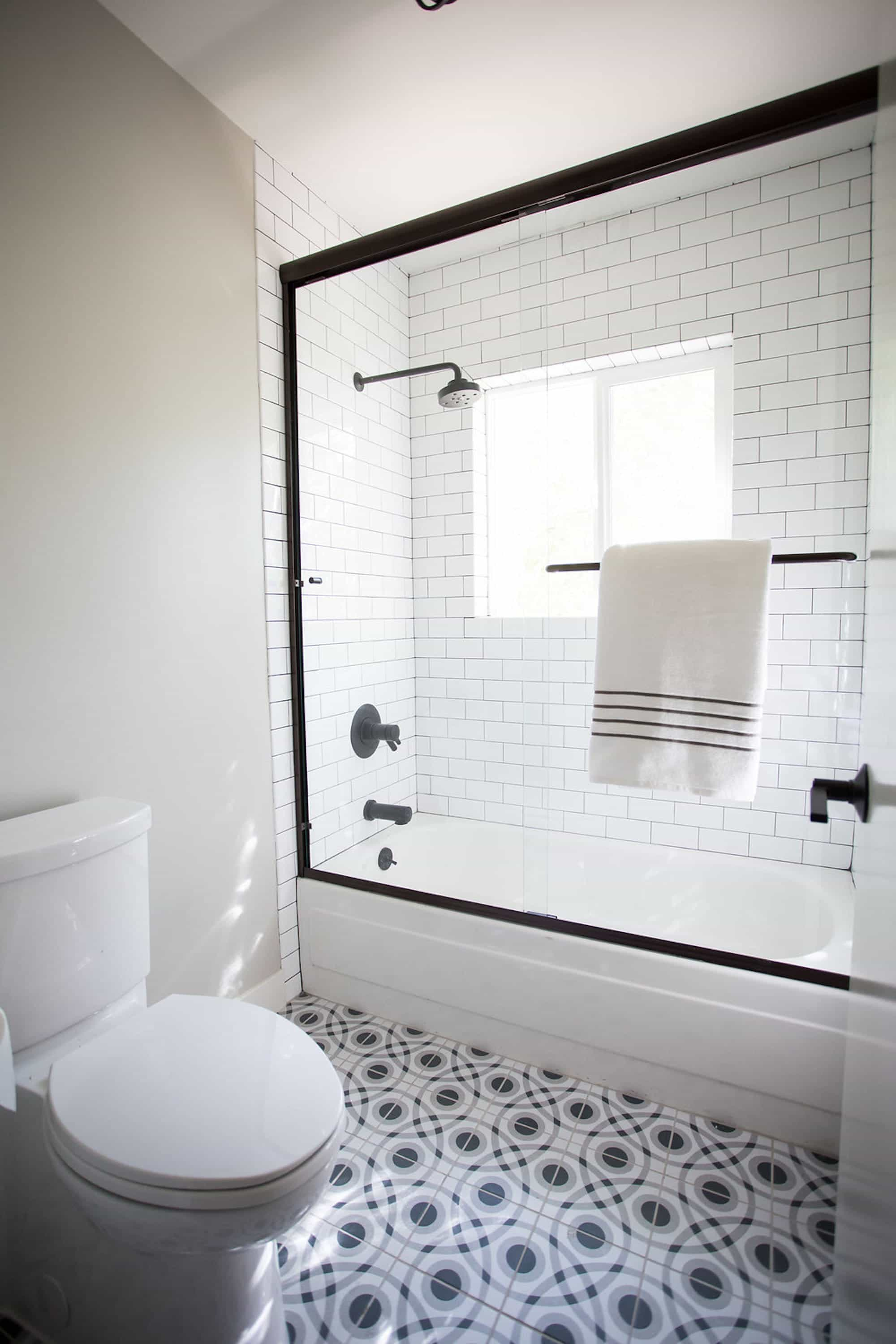 Black And White Bathroom With Patterned Floor Tile And Subway Tile Glass Door Shower (Image 3 of 16)