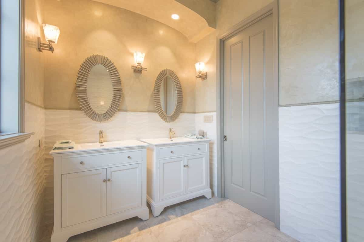 Oval Mirrors Over White Cabinets And Trio Of Sconces Light (Image 17 of 20)