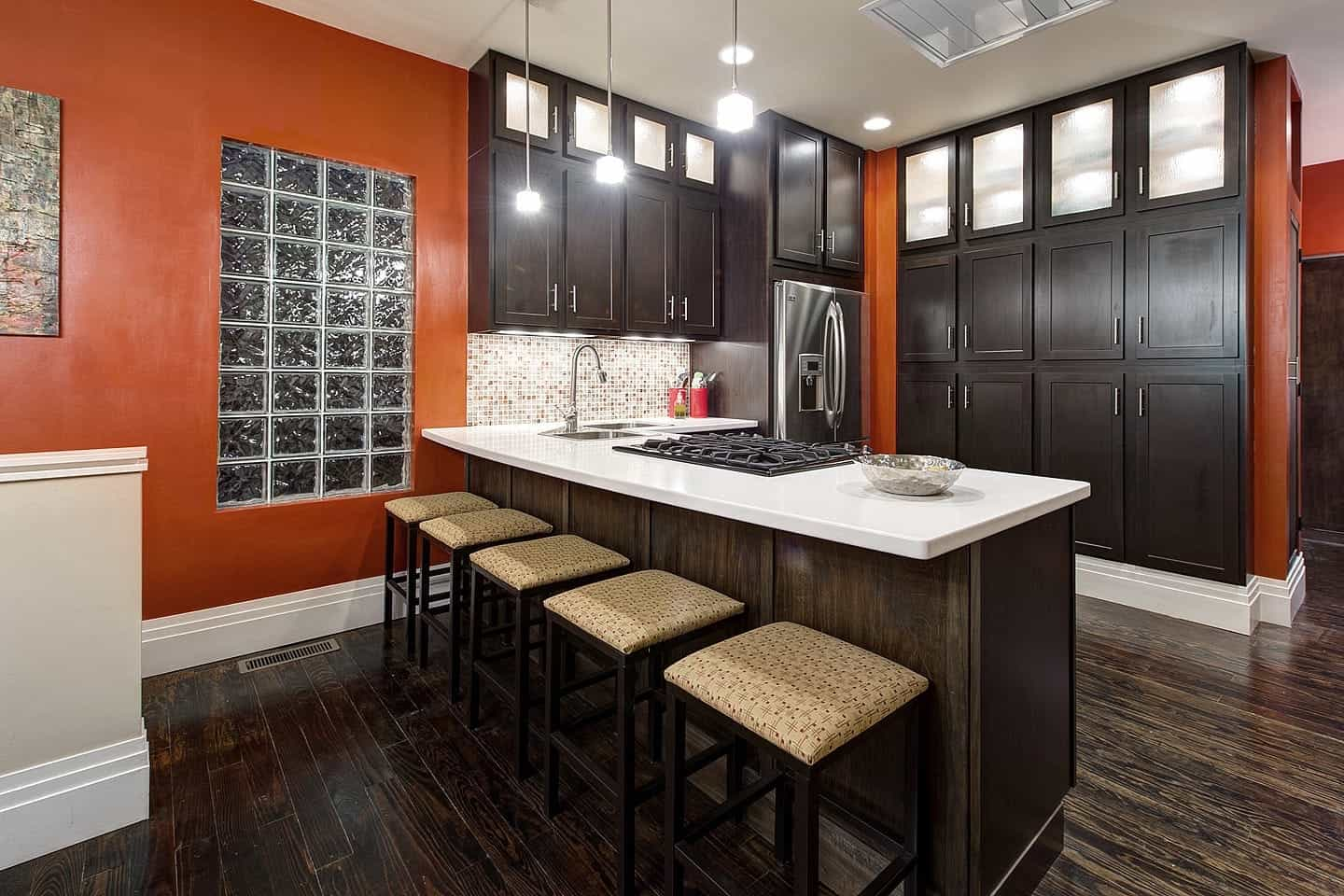 Bold Orange Kitchen Features Dark Wood Cabinetry And Dark Wood Flooring (Image 3 of 12)