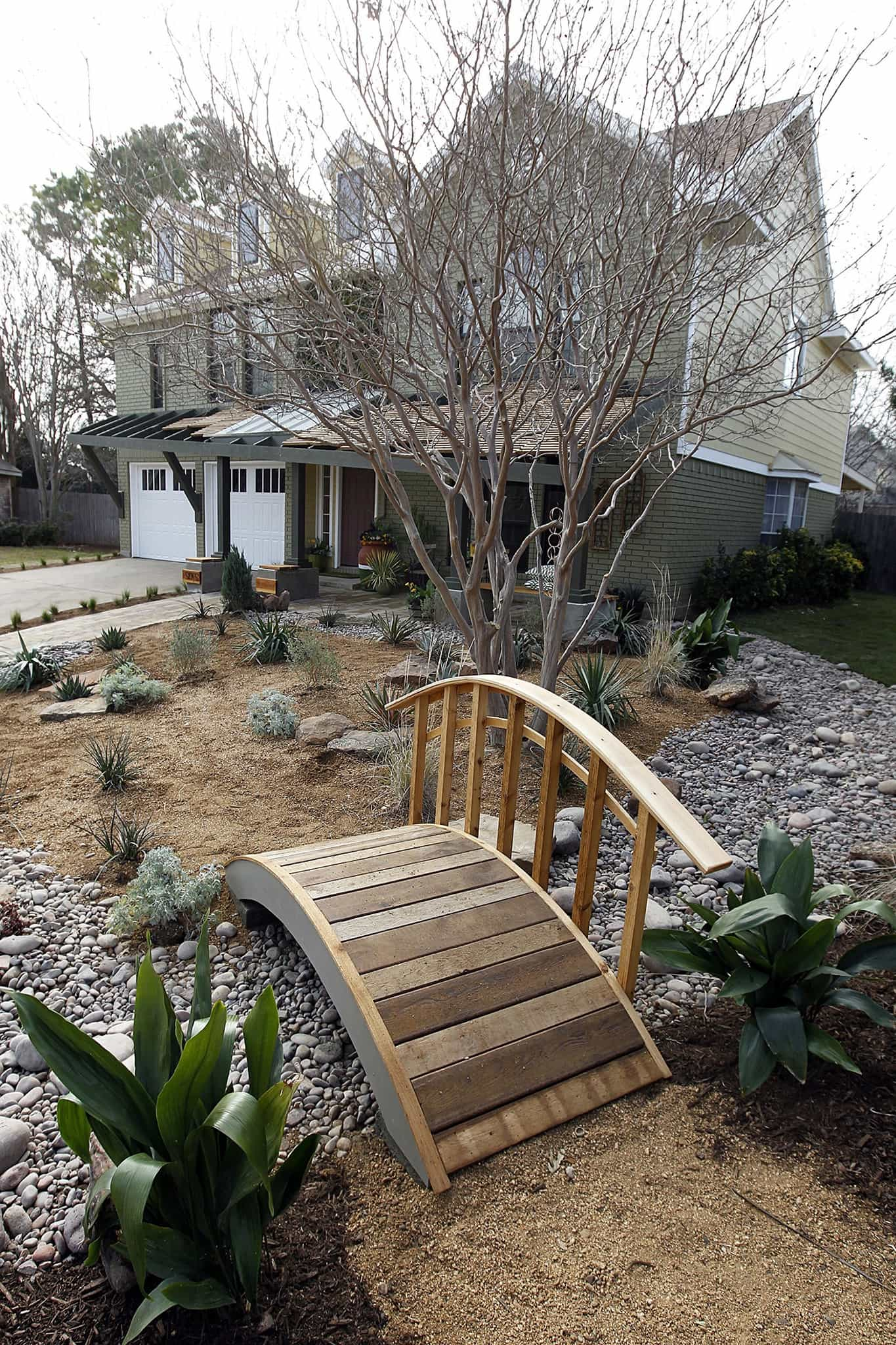 Featured Image of Cape Cod Style Home With Curved Wooden Bridge Over Xeriscaped Yard