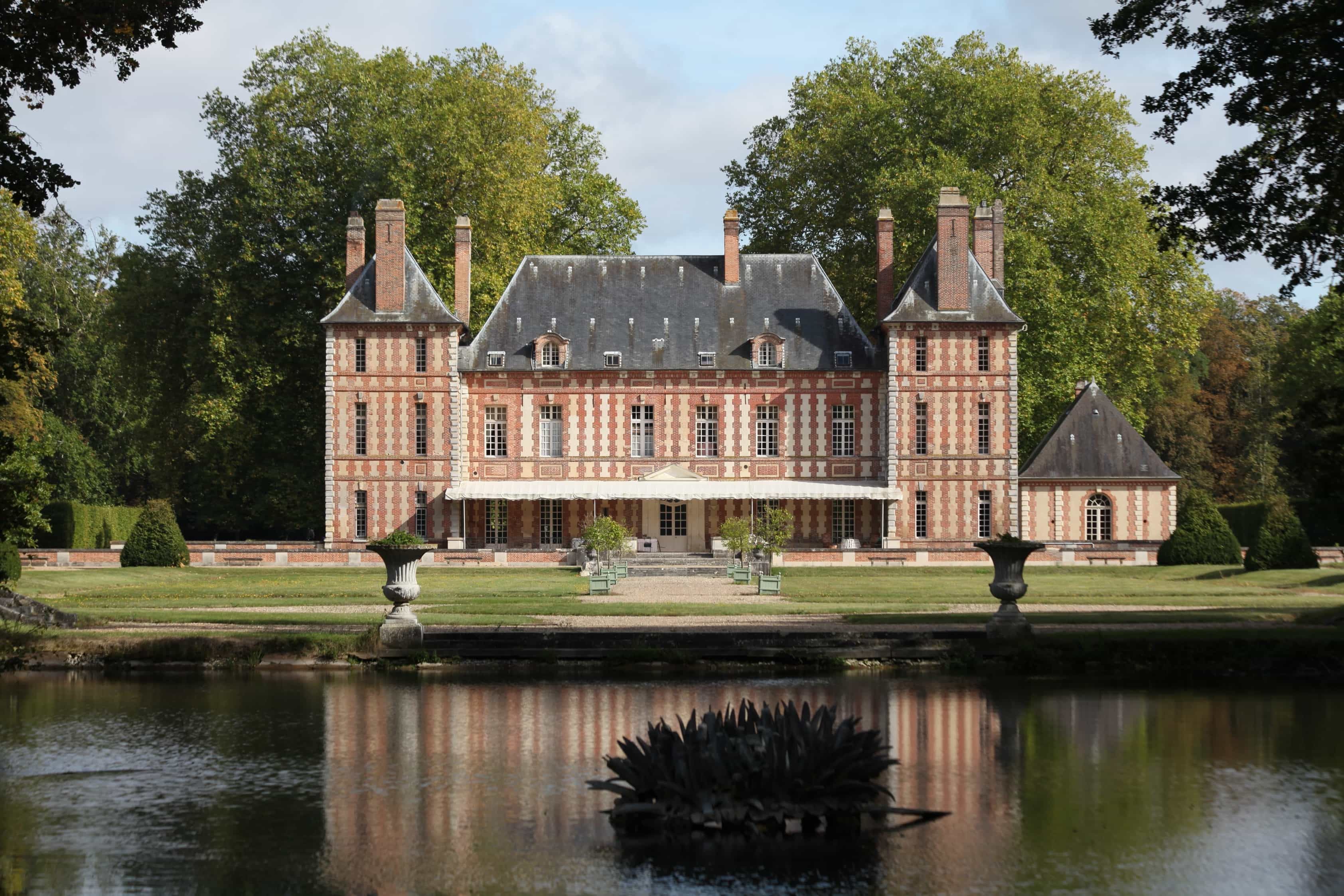 Featured Image of French Colonial House Exterior With Striped Brick And Tranquil Pond