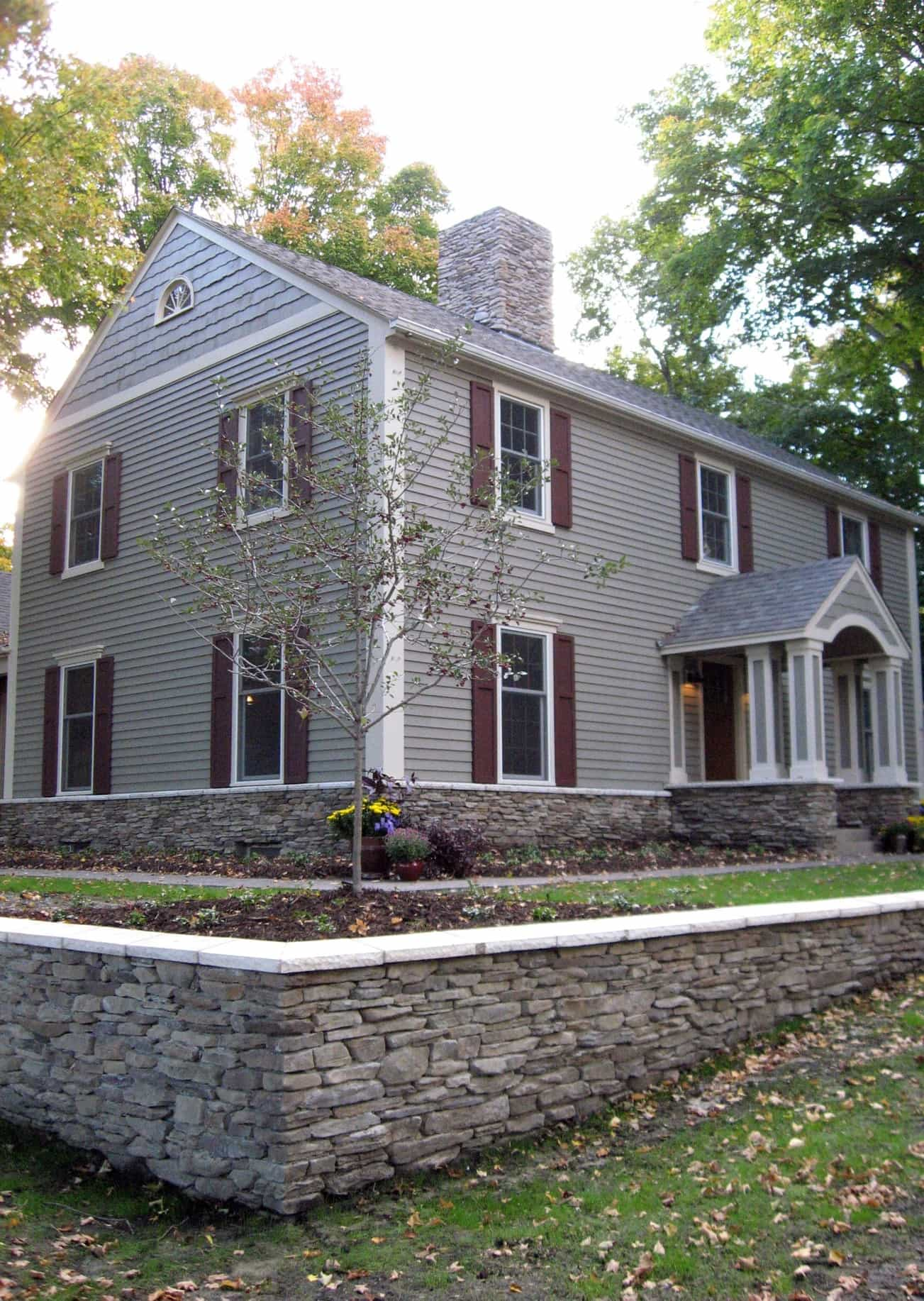 Featured Image of Gray Colonial Home With Dark Red Shutters