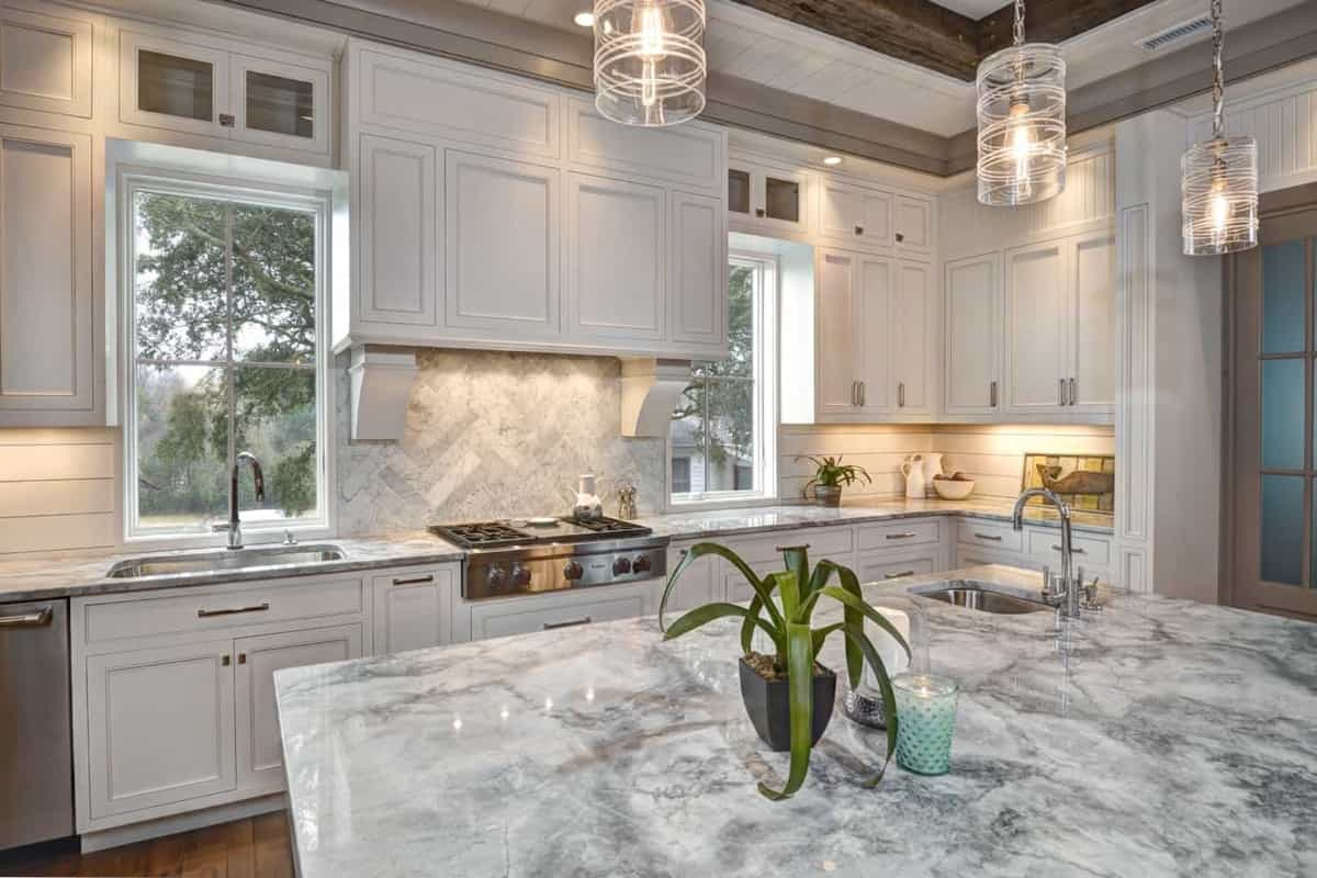 Featured Image of White Kitchen With Large Marble Topped Island And Expansive Cabinets