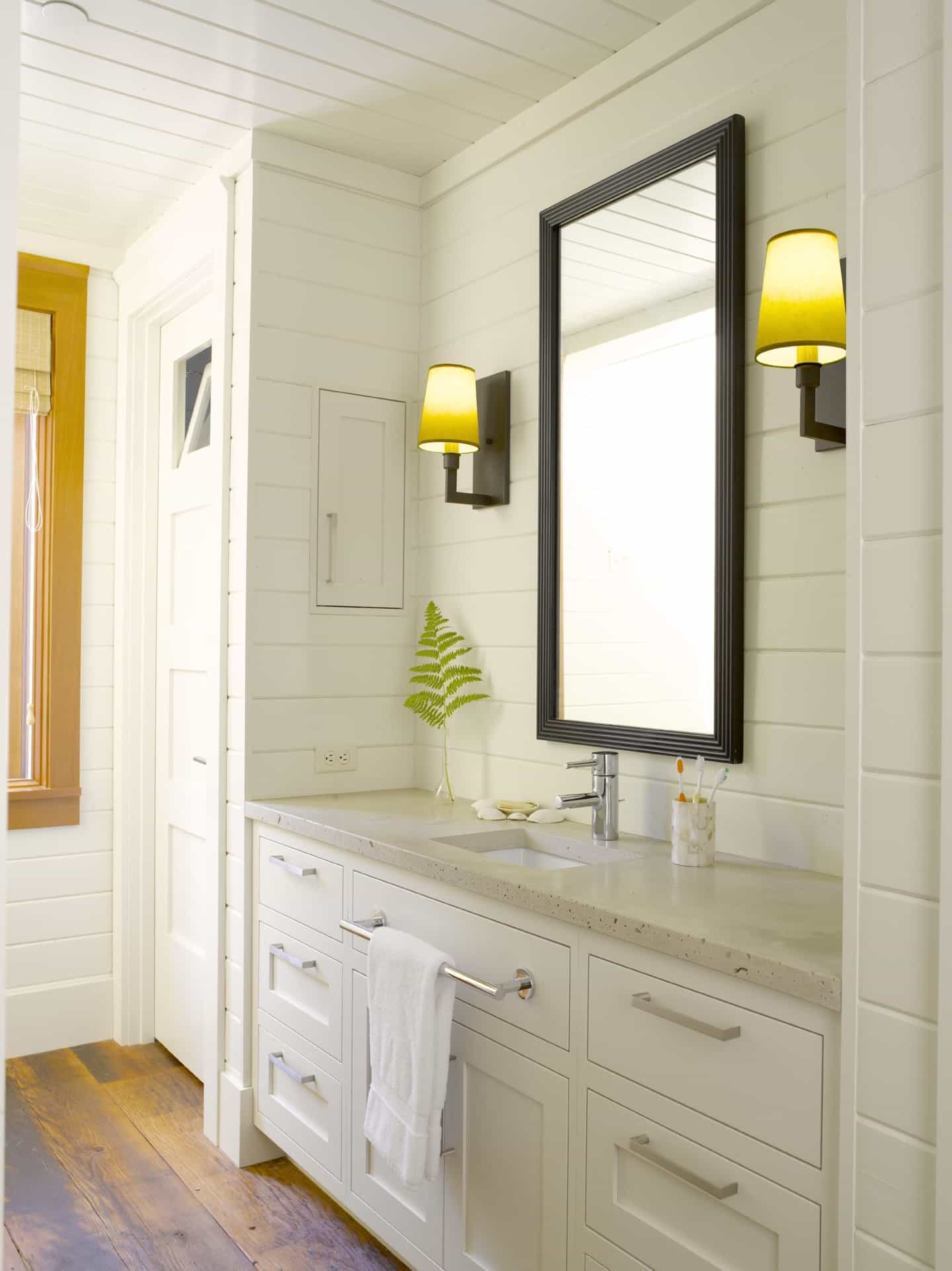 Featured Image of Bright Cottage Bathroom Features Wall To Ceiling White Paneling And A Single Vanity