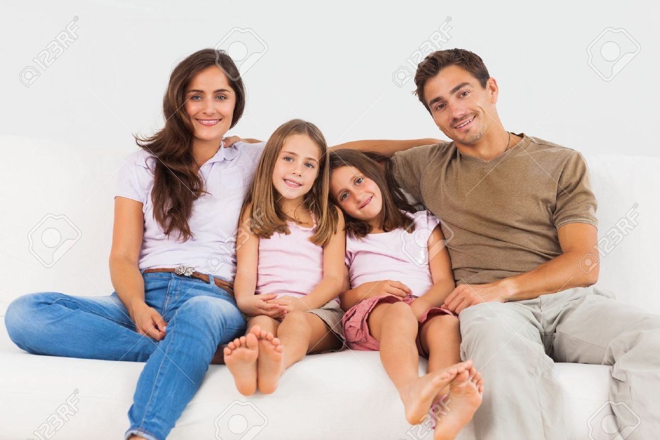 Cute Family Sitting On A Sofa In The Living Room Stock Photo Inside Family Sofa (Image 2 of 15)