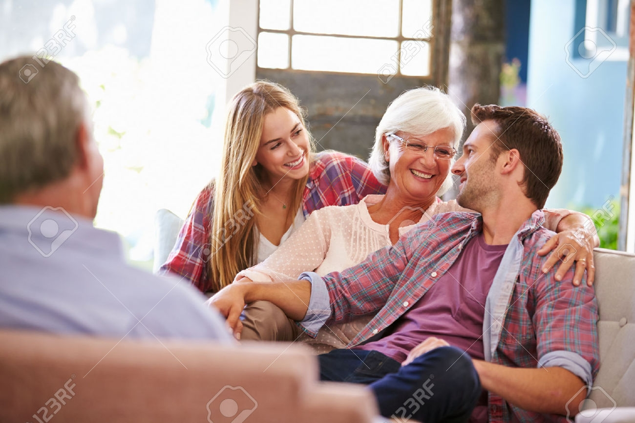 Family With Adult Children Relaxing On Sofa At Home Together Stock Regarding Family Sofa (Image 7 of 15)