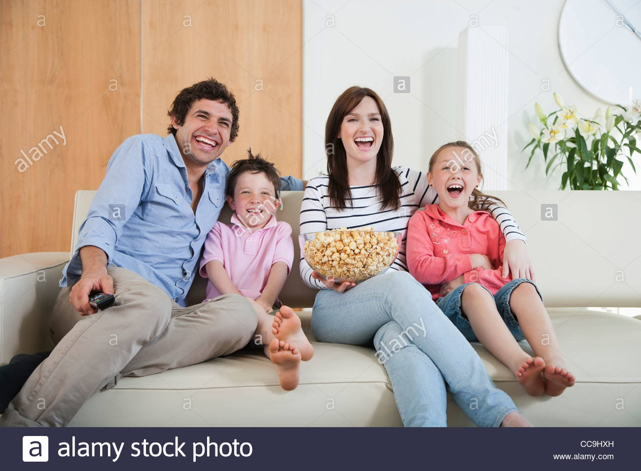 Laughing Family Watching Tv On Sofa Stock Photo Royalty Free Within Family Sofa (Image 11 of 15)