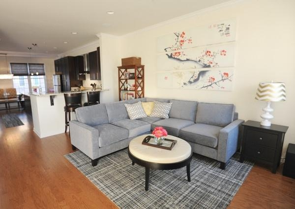 The Living Room Features A Soft Gray Sectional Sofa (View 17 of 20)