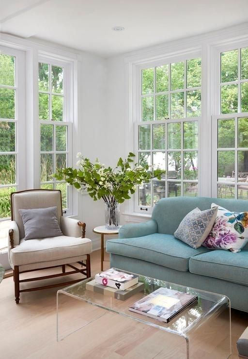 Sun Filled Living Space Is Filled With A Blue Roll Arm Sofa Facing A Pertaining To Peekaboo Acrylic Coffee Tables (Image 38 of 40)