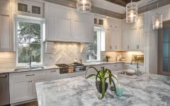 White Kitchen With Large Marble Topped Island and Expansive Cabinets