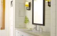 Bright Cottage Bathroom Features Wall to Ceiling White Paneling and a Single Vanity