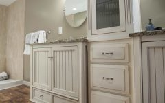 Cottage Twin Vanities With Round Mirrors and Cabinet Lighting